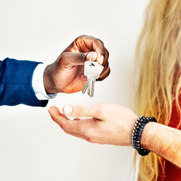 man handing keys to woman